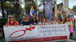 Activists from Associazione Transessuale Napoli stand behind a banner, waving flags.