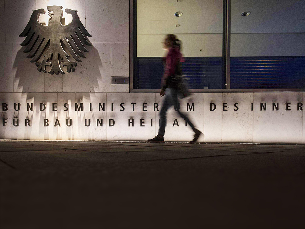 A person is seen walking in front of the building of the German Federal Ministry of the Interior.