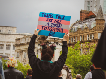 """Protest sign with the colours of the trans flag that says, """"Trans folx are not a threat. Transphobia is."""""""